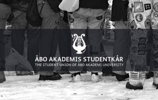 En rad med studerande i halare, ÅAS logo