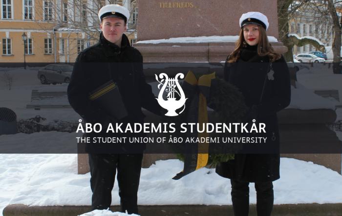 Styrelseordförande Joonas Karlsson och generalsekreterare Jasmin Öberg står ute i mörka kläder och håller i en krans