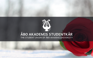 En ros som ligger på snön. ÅAS logo./ A rose on snow. The Student Union's logo.