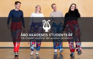 Fyra studerande har halare på sig, går mot kameran och skrattar