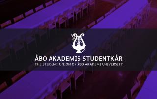 Bild på en tom festsal i mörklila, ÅAS logo.